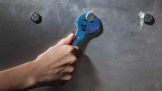 Mann mit Werkzeug an einer Wand
