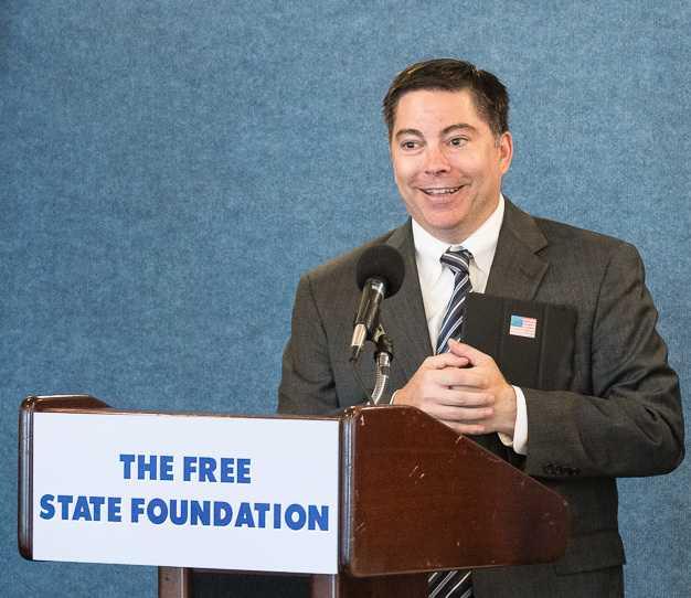 "Michael O'Rielly an Rednerpult mit Aufschrift ""The Free State Foundation"""