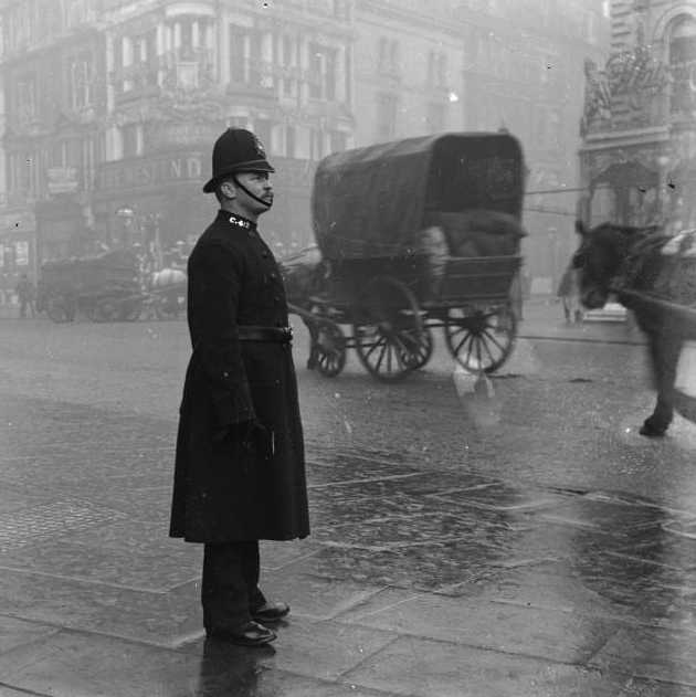 Altes Foto eines Polizisten im Regen, dahinter Pferdefuhrwerke