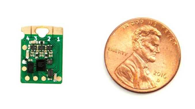 Ein US-amerikanischer Cent neben einer kleineren, grünen Platine mit wenigen Bauteilen.