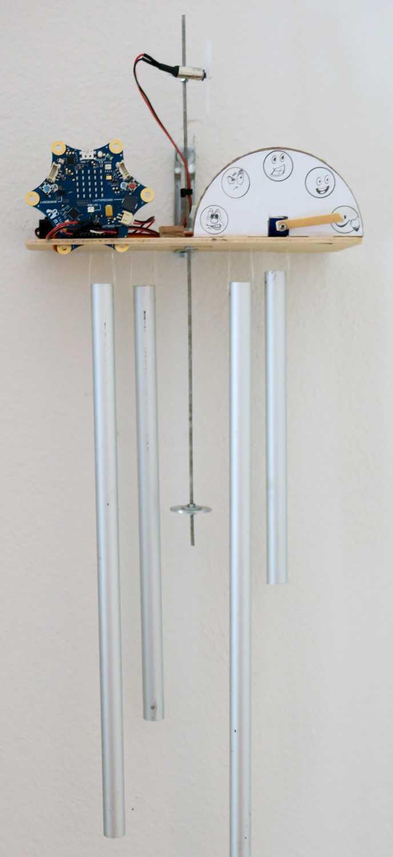 Auf einem Holzbrett stehen ein sternförmiger Calliope mini und eine Anzeige mit verschieden zufriedenen Gesichtern. Durch das Holz geht ein Pendel mit Propeller und unten hängen vier Metallrohre.