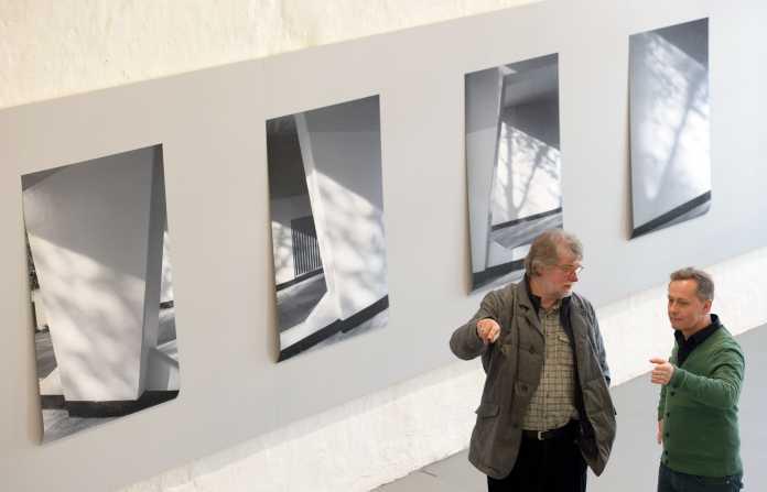 """Der Fotograf Tomek Mzyk (r) und Fotografie-Professor Rolf Nobel unterhalten sich am 27.02.2014 in Hannover (Niedersachsen) in der Fotoausstellung """"Archideologie""""."""
