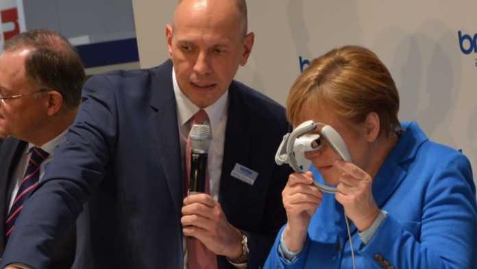 Merkel begutachtet Datenbrille von Brother
