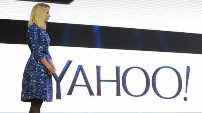 Marissa Mayer neben Yahoo-Logo