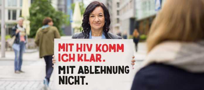 """Frau hält Schild """"Mit HIV komm ich klar. Mit Ablehnung nicht."""""""