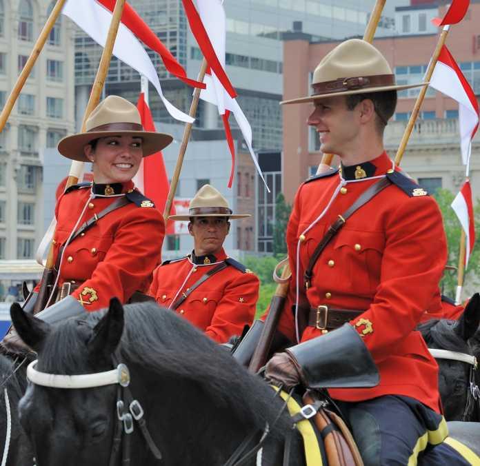 Drei rot uniformierte Polizisten zu Pferd