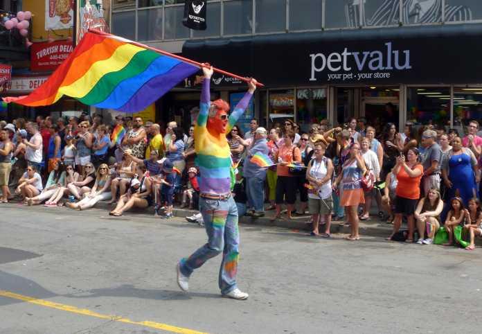 Mann mit in Regenbogenfahnen bemaltem Oberkörper schwenkt große Regenbogenfahne, dahinter stehen Schaulustige Spalier