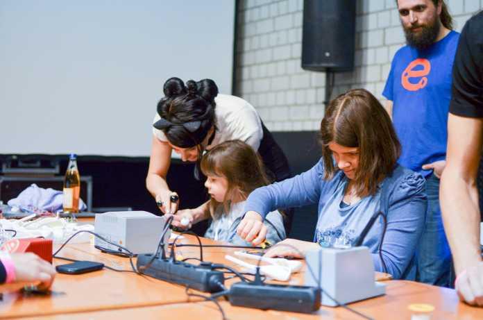 Zwei Mädchen arbeiten an einem Tisch mit Lötkolben. Eine Frau mit schwarzen Haaren und Katzenohr-Haarreif beugt sich zu einer der Beiden herunter.