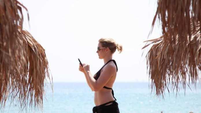 Mit dem Handy am Strand