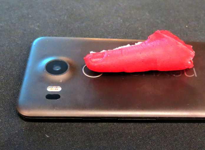 Roter Fingerklon aus Silikon liegt auf Handy-Rückseite, Fingerabdruck berührt Sensor