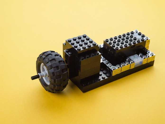 Ein Lego-Rad neben schwarzen und silbernen Steinen