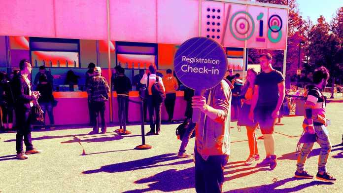 """Mann hält sich Schild """"Registration Check-In"""" vors Gesicht. Dahinter Check-In-Schalter der Google I/O 2018"""