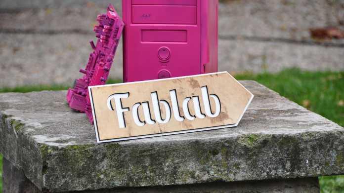"""Schild """"Fablab"""" vor einem rosa angesprühten Rechner"""