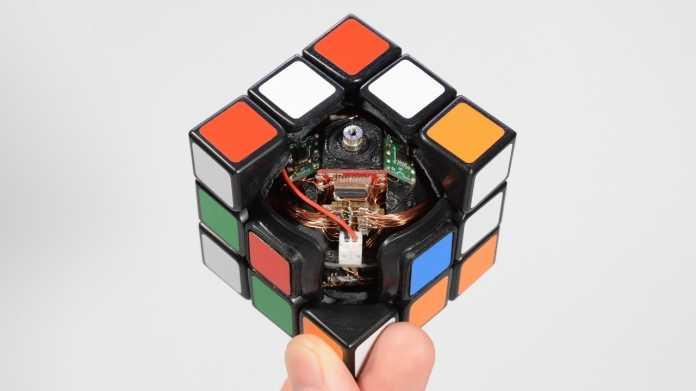 Eine Hand hält einen geöffneten Zauberwürfel mit elektronischem Innenleben hoch