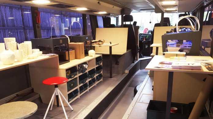 Umgebauter Bus, in dem innen Arbeitsplätze, 3D-Drucker und Regale stehen