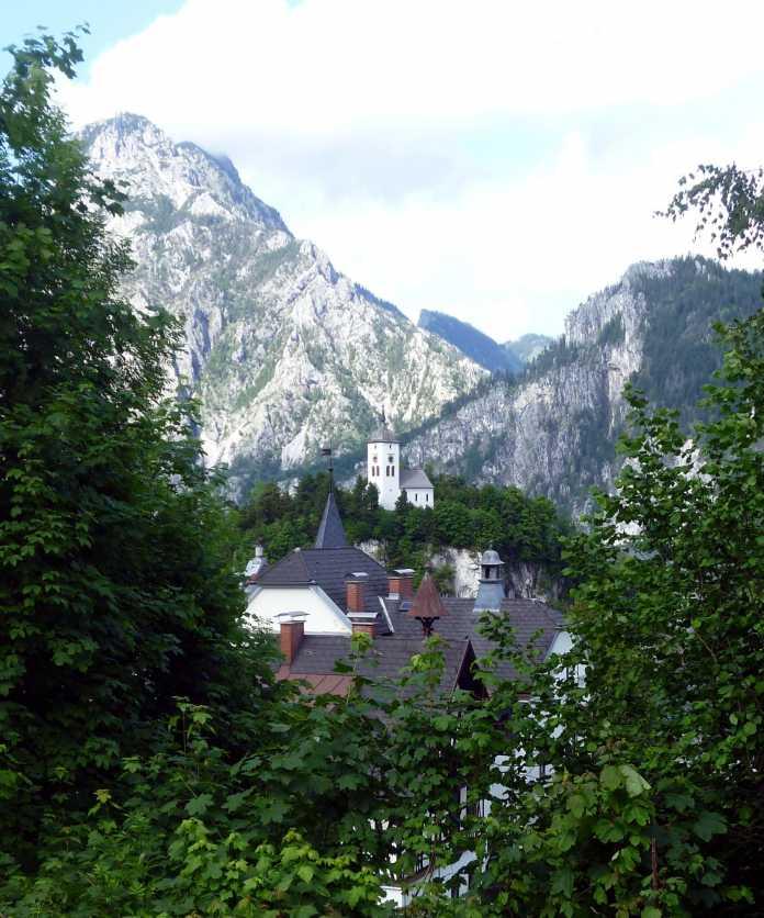 Aussicht auf Dorf mit Kirche auf einem Hügel, dahinter Alpen