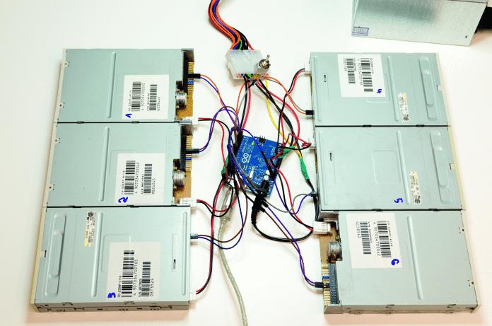 Sechs Diskettenlaufwerke, um einen Arduino verteilt.