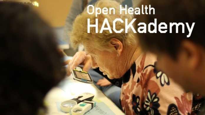 Eine ältere Dame beugt sich mit einer Handy-Lupe über zwei Lupen.