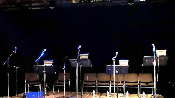 Bühne mit Mikrofonständern und Notenpulten ohne Menschen