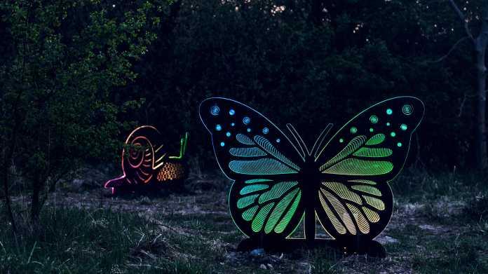 Eine überlebensgroße Schnecke und Schmetterling stehen als beleuchtete Metallskulpturen zwischen Sträuchern.