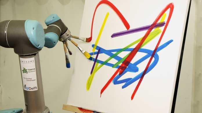 Ein Roboterarm hält vier Pinsel mit Farbe vor einer Leinwand.