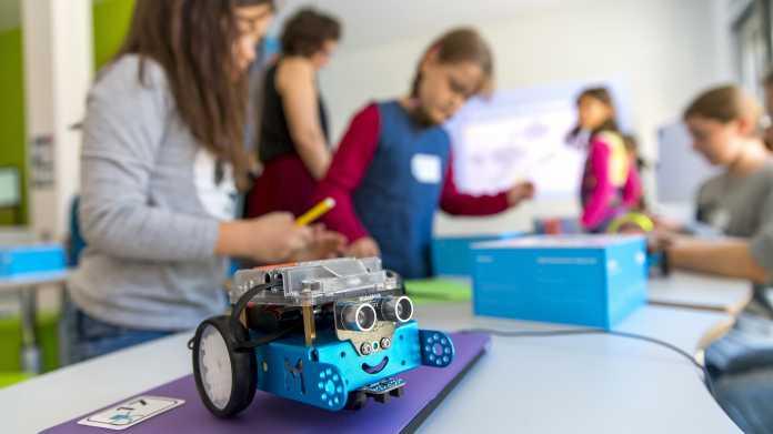 Vorn ein blauer Roboter mit schwarzen Rädern, im Hintergrund sind fünf Kinder.