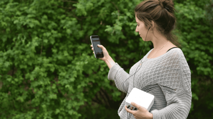 Eine Frau hält eine weiße Kiste und ein Smartphone.