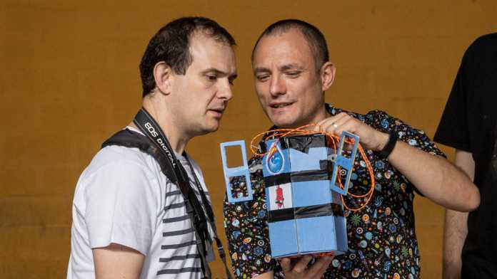 Zwei Männer schauen auf einen blauen Kasten mit zwei kleinen Antennen.