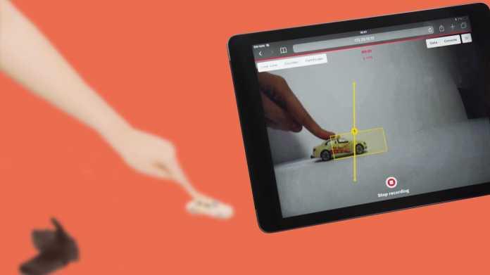 Eine Hand schiebt im Hintergrund ein Spielzeugauto - im Vordergrund ist das Bild auf einem Tablet zu sehen, wobei das Auto mit einem gelben Rahmen markiert ist.