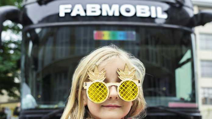 Ein Kind mit gelaserter Scherz-Brille vor dem Fabmobil.