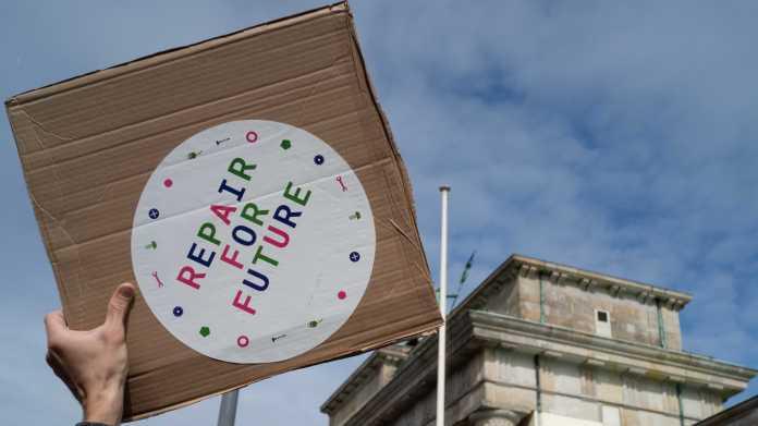 """Vor dem Bundestag hält eine Hand ein Schild """"Repair for Future"""" in die Luft."""