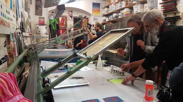 In einer Siebdruckwerkstatt stehen mehrere Menschen.