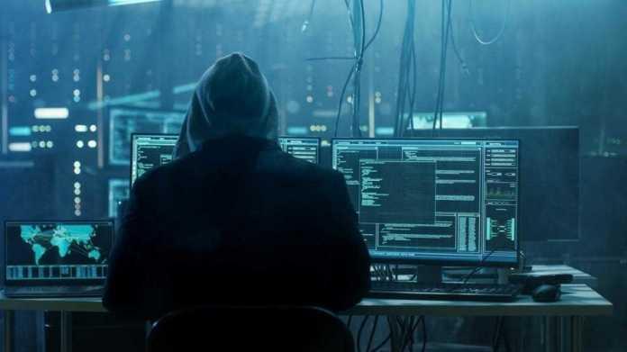 Person mit Kapuze sitzt vor Computern