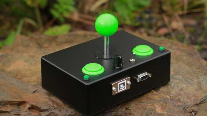 Ein schwarzes, rechteckiges Gehäuse aus Metall, aus dem zwei grüne Buttons, ein Kippschalter, ein Potentiometer und ein grüner Joystick ragen.