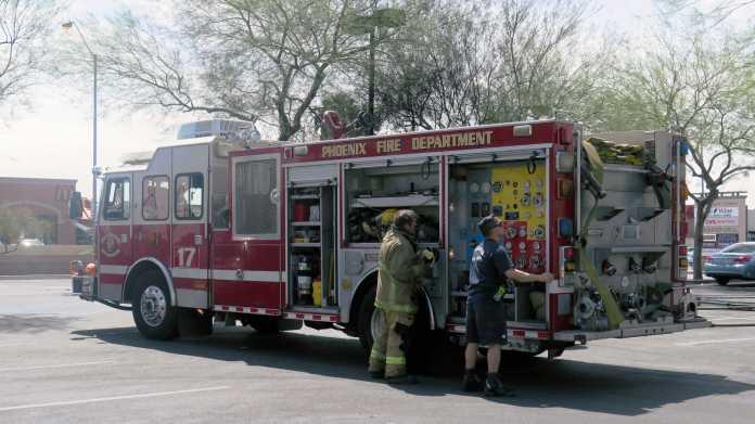 Löschfahrzeug der Feuerwehr Phoenix', davor zwei Feuerwehrmänner