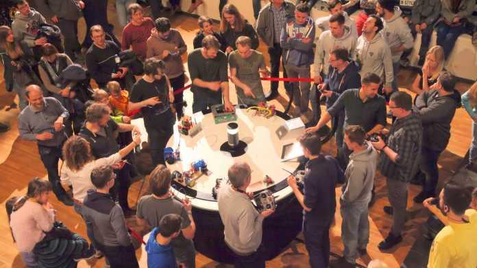 Viele Menschen stehen um eine runde, weiße Arena mit Robotern drin.