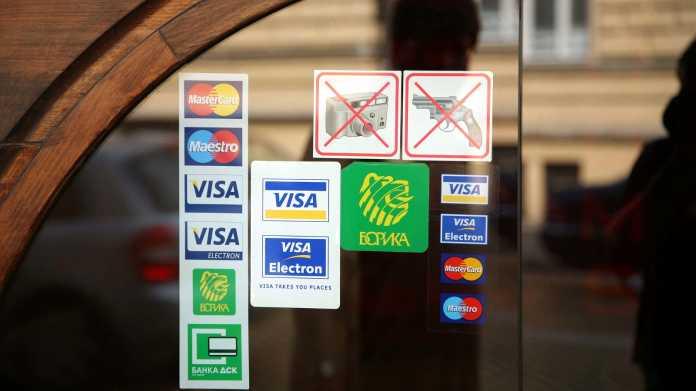 Glstüre mit Aufklebern, die die Akzeptanz verschiedener Karten signalisieren, darunter mehrere VISA-Karten