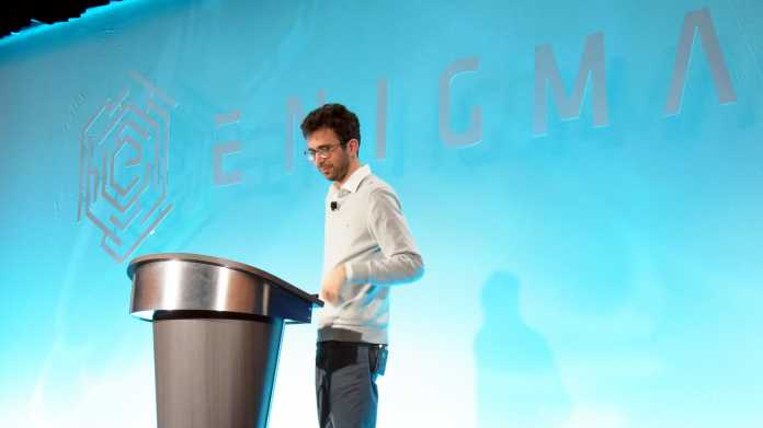 """Schlanker weißer Mann in hellem Pullover an Rednerpult, dahinter hellblaue Wand mit Schriftzug """"ENIGMA"""""""