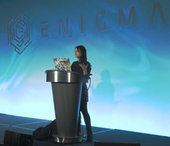 """Frau an Rednerpult, dahinter blaue Wand mit Schriftzug """"Enigma"""""""
