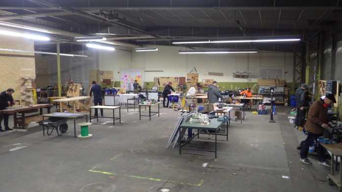 Eine Halle mit vielen Tischen, an denen Menschen arbeiten.