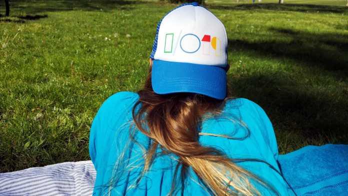 Rückensicht einer blonden Frau, die eine Google-I/O-2019-Kappe tragend im Gras liegt