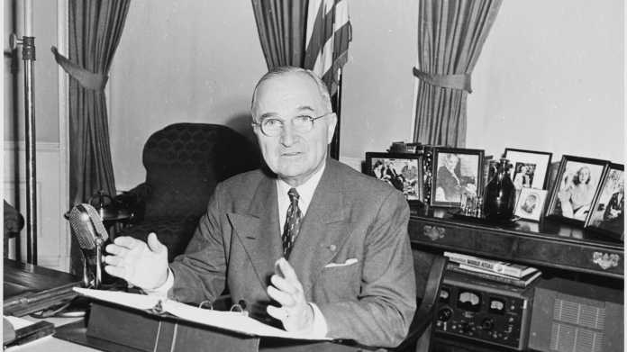 Harry S. Truman an Schreibtisch sitzend