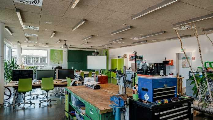 Ein großer Raum mit Bildschirmarbeitsplätzen und Werkbanken.