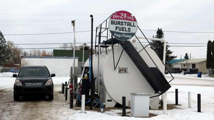 """Ein schwarzer Honda CRV steht neben einem großen, weißen, runden Treibstofftank, auf dem Schilder """"Burstall Fuels"""" sowie """"For Sale"""" montiert sind. Es liegt Schnee."""