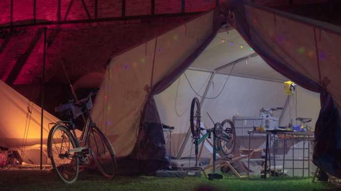 In einem großen, beleuchteten Zelt steht ein umgedrehtes Fahrrad.