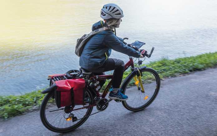 Finn mit Fahrradhelm auf dem E-Bike, auf einem Radweg an einem Flussufer.