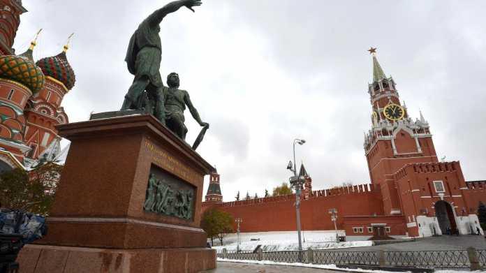 Bronzestatue am Roten Platz in Moskau vor dem Erlöserturm des Kreml und der Basilius-Kathedrale (am linken Bildrand)
