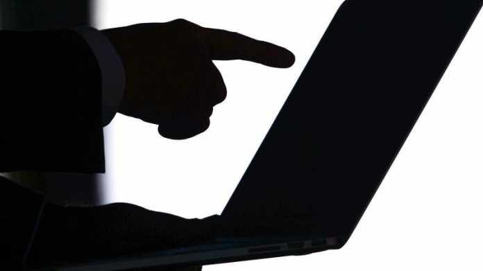 Finger zeigt auf Laptopbildschirm