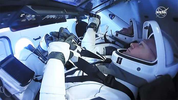2 Männer liegen in weißen Astronautenanzügen