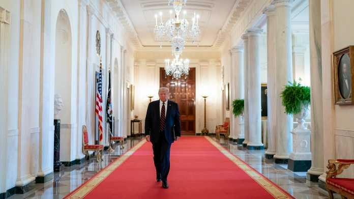 Donald Trump geht auf rotem Teppich durch weißen Gang